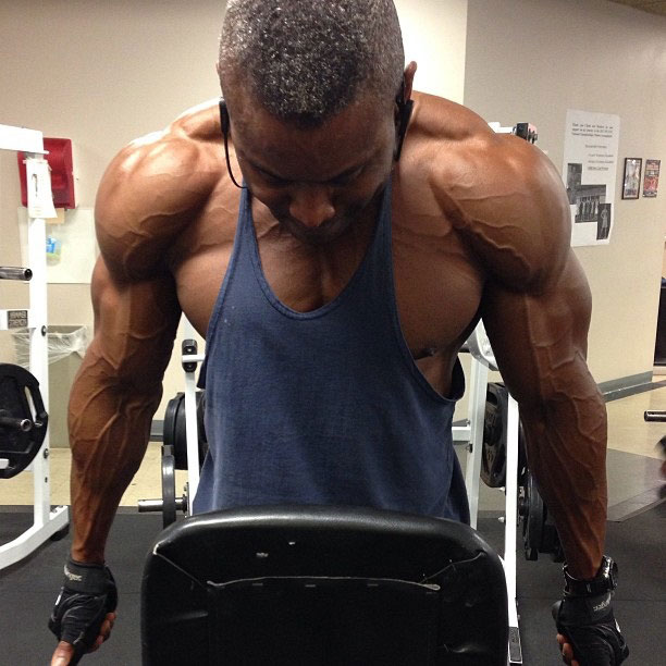 Michael Anderson performing tricep dips in the gym.