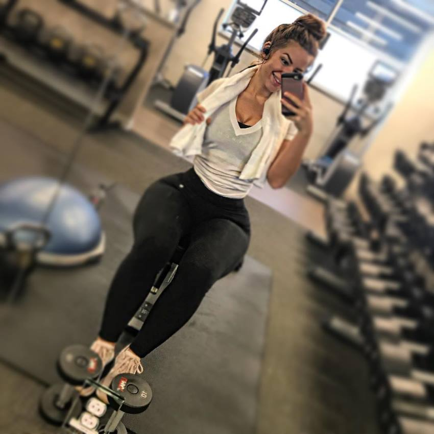 Mindy Sittinpretty taking a selfie in the gym by the dumbbell rack