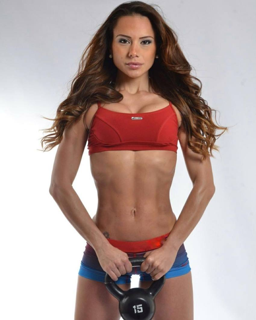Nathalia Melo posing for a photo with a kettlebell in her hand