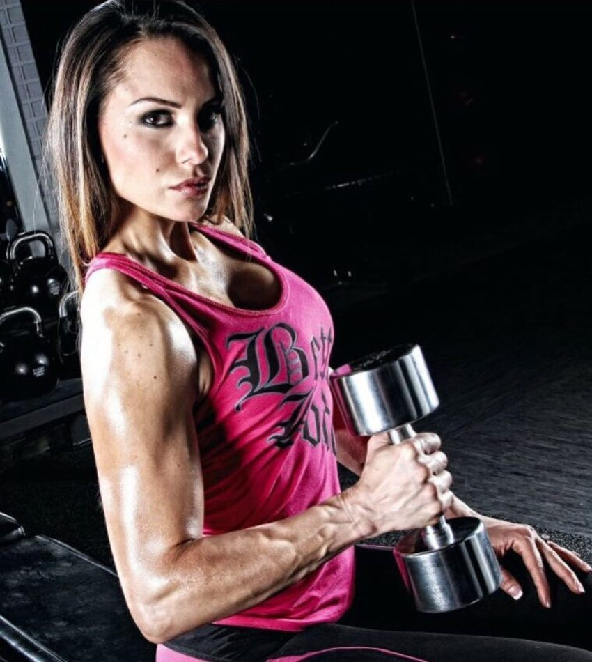 Nathalia Melo with a dumbbell in her hand looking directly at the camera