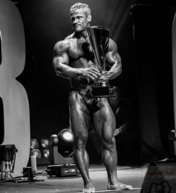 Nicolas Vullioud standing on the bodybuilding stage with a trophy in his arms