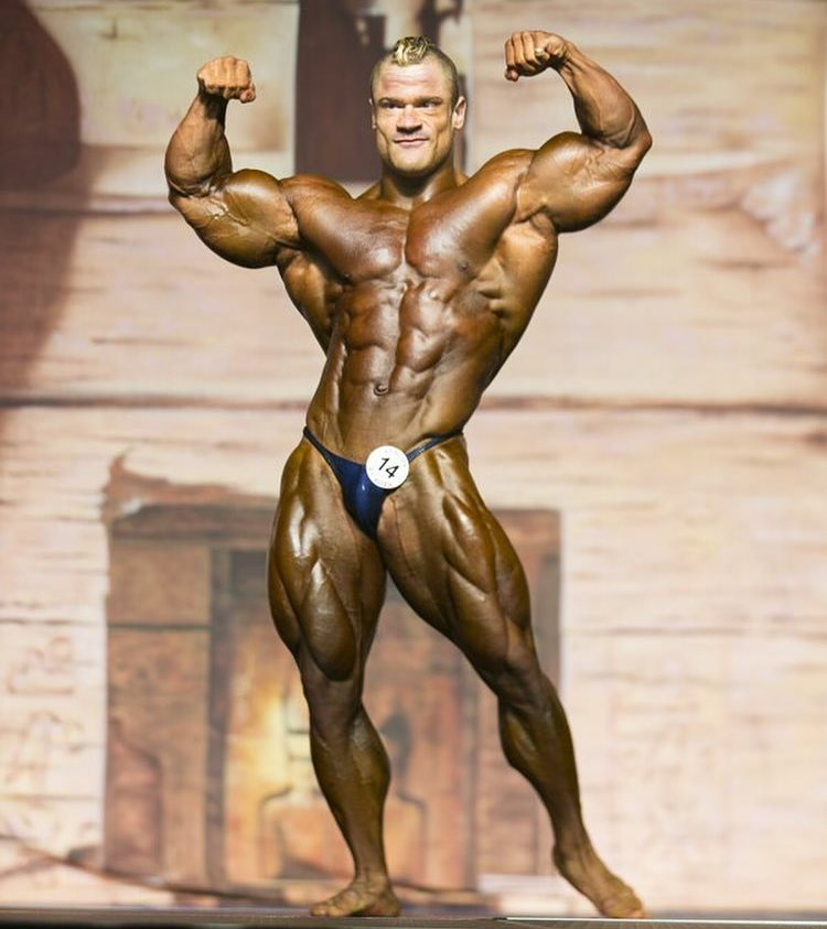 Nicolas Vullioud doing a front double biceps pose on the bodybuilding stage