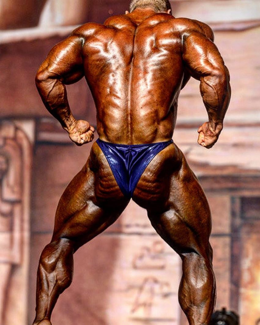 Nicolas Vullioud flexing his ripped back on the bodybuilding stage