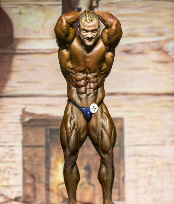Nicolas Vullioud flexing his abs and legs on the bodybuilding stage, showing off his impressive conditioning