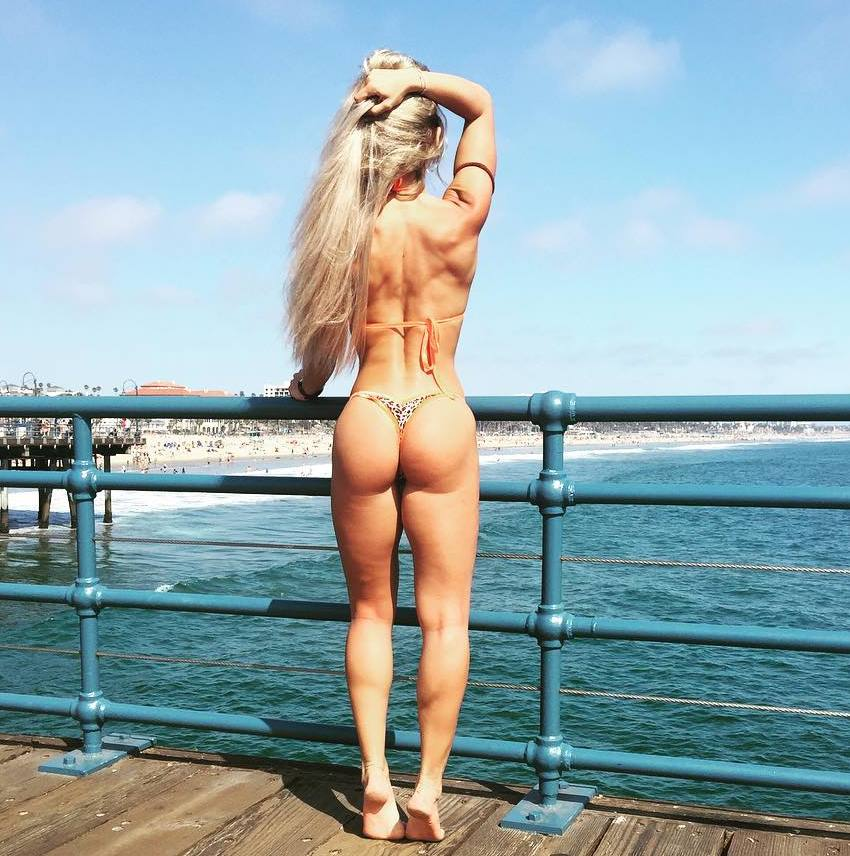 Nikola Weiterova standing on the pier by the sea showcasting her curvy legs and glutes