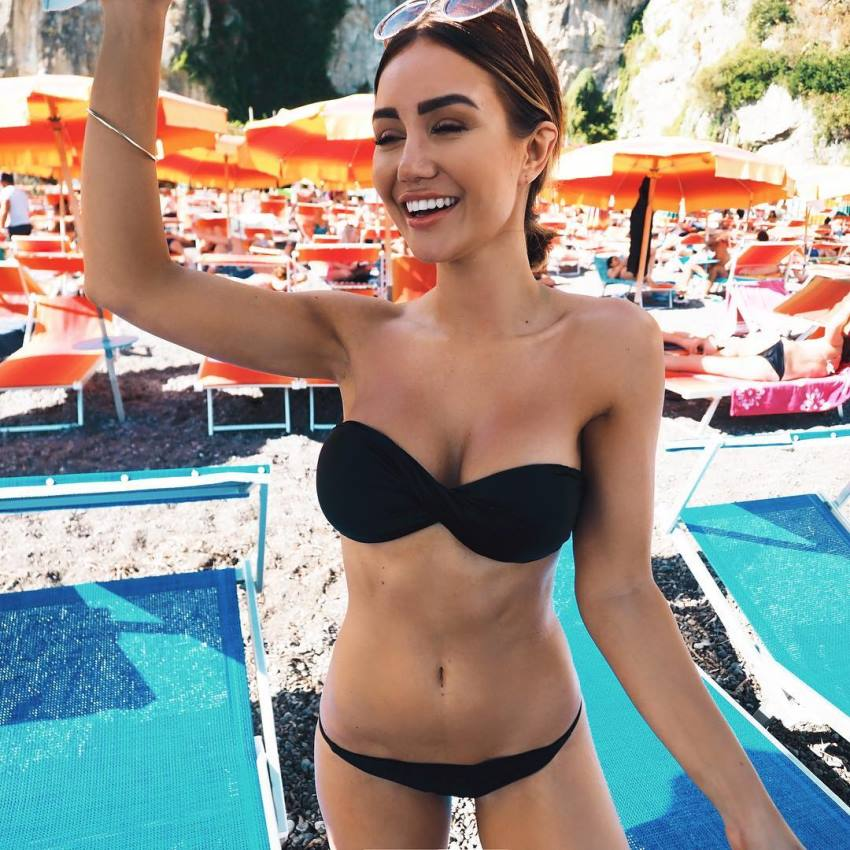 Pia Muehlenbeck enjoying her time by the pool smiling at the distance