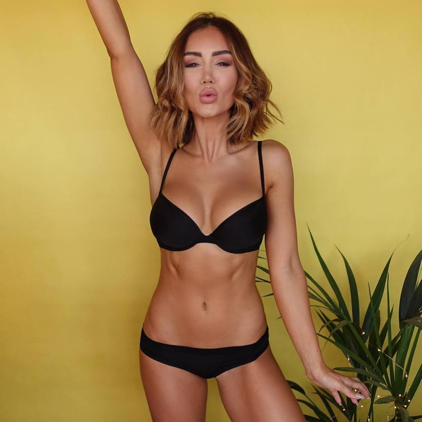 Pia Muehlenbeck with one of her hands raised up in the iar showing her lean and fit body