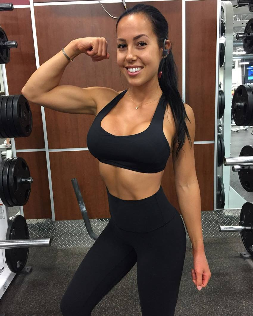 Randi Kennedy flexing her biceps in the gym and smiling at the camera