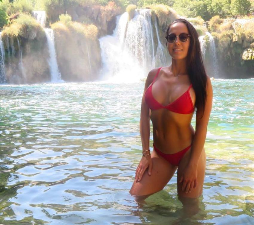 Randi Kennedy enjoying the nature wearing a red bikini standing in the water and smiling at the camera