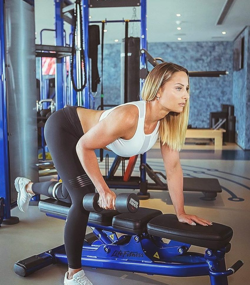 Rebecca Burger doing dumbbell bent over rows in a gym