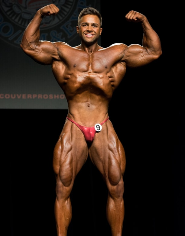 Regan Grimes flexing his biceps on the bodybuilding stage, looking conditioned and muscular