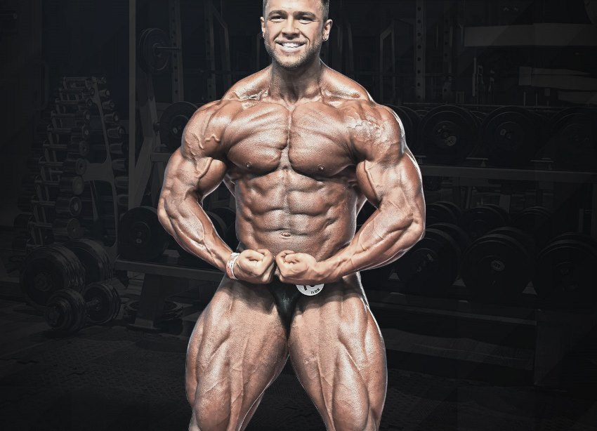 Regan Grimes performing a most muscular pose, looking ripped and huge