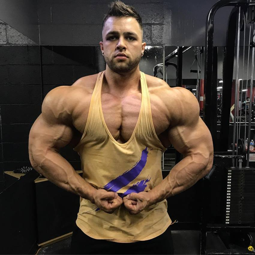 Regan Grimes flexing his arms and shoulders in a yellow tank top
