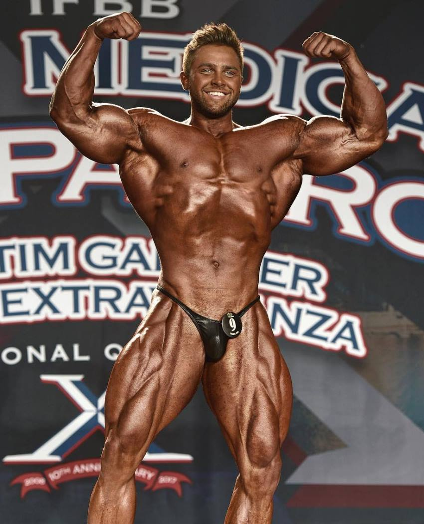 Regan Grimes flexing front double biceps on the boybuilding stage