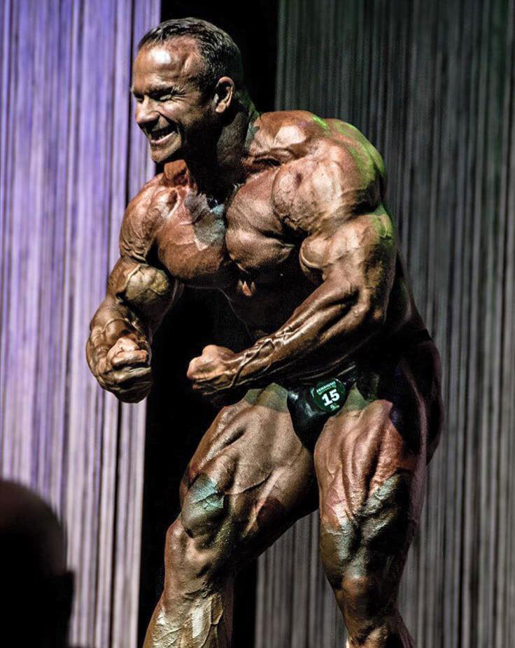 Ronny Rockel flexing his arms on the bodybuilding stage.