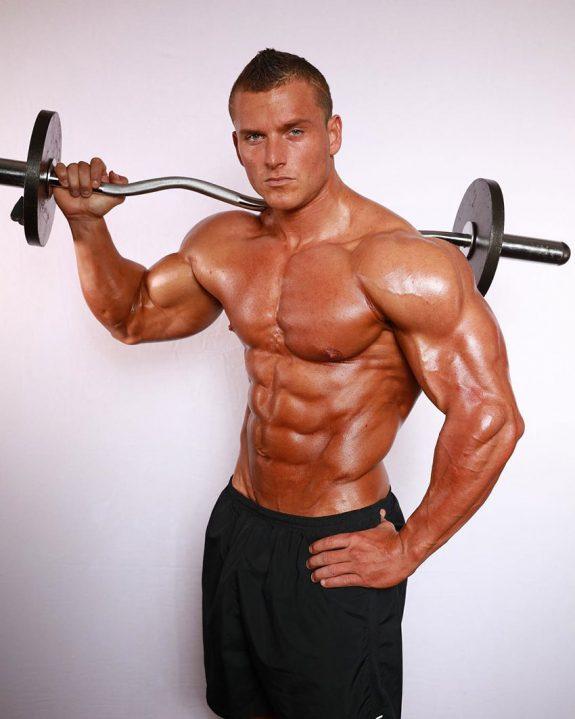 Samuel Dixon holding an EZ Bar over his shoulders.