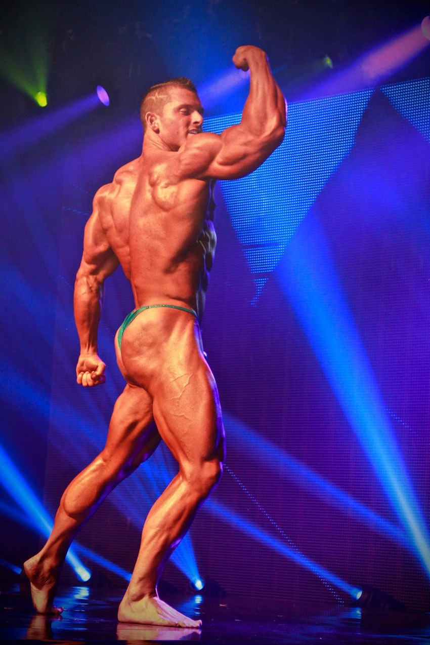 Samuel Dixon flexing his bicep on stage.