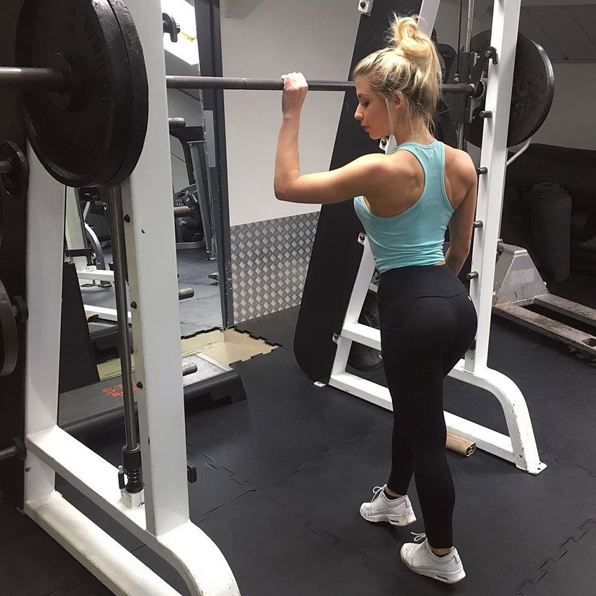 Sophie Aris holding onto a barbell in the gym.