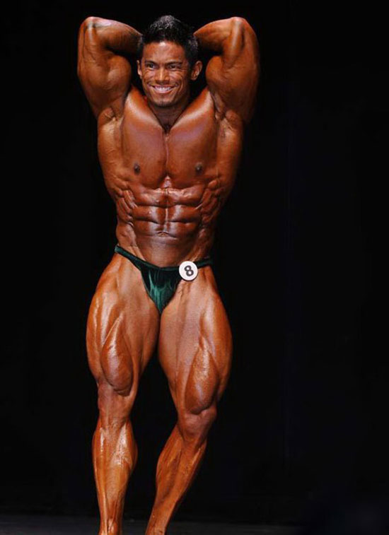 Stan McQuay posing on the bodybuilding stage.