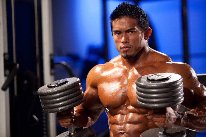 Stan McQuay holding dumbbells in a photo shoot.