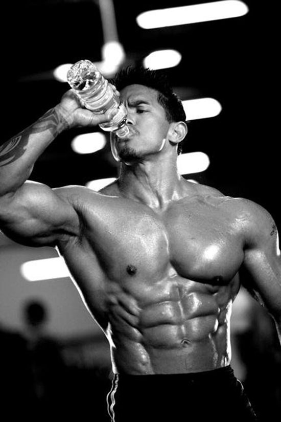 Stan McQuay drinking out of a water bottle showing off his abs.