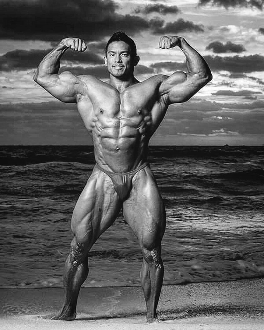Stan McQuay flexing his arms on the beach.