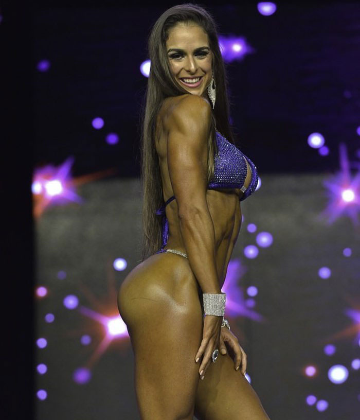 Stephanie Sequeira posing on the bodybuilding stage.