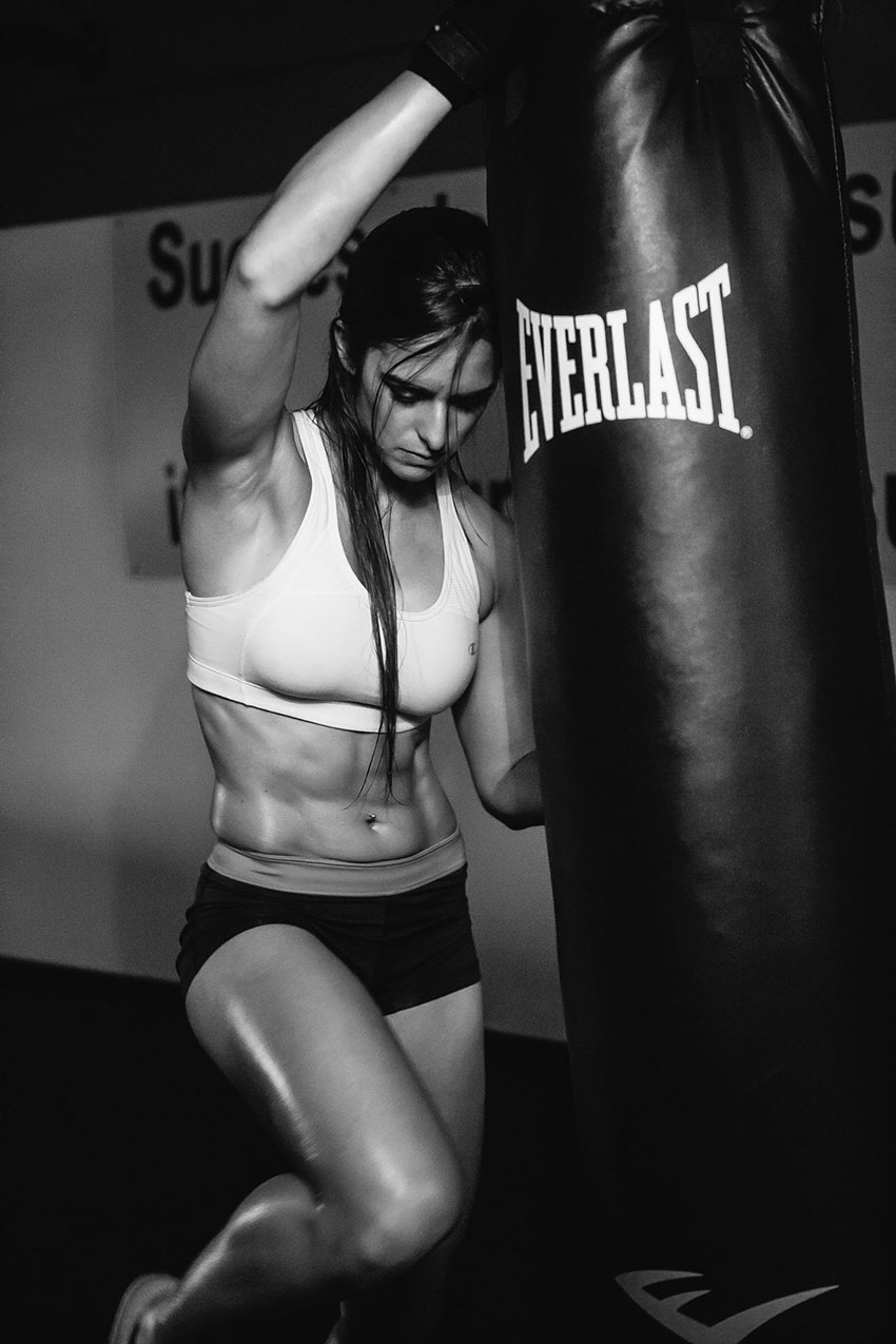 Stephanie Sequeira leaning on a punch bag in a photo shoot.