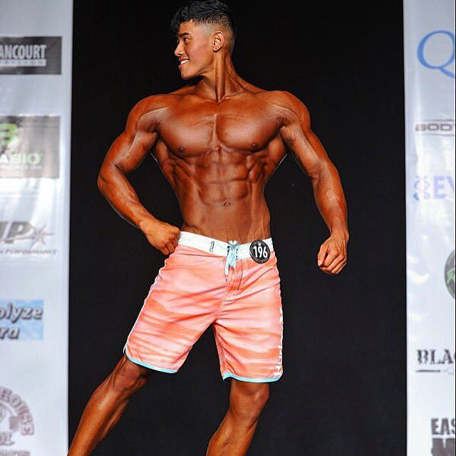 Steven Cao posing on the Men's Physique stage