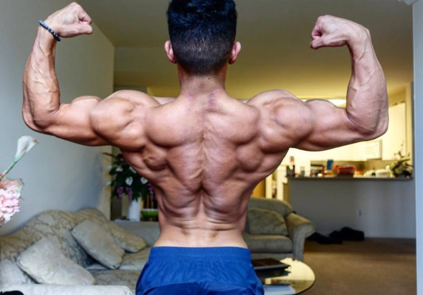 Steven Cao doing a back double biceps pose in living room, looking ripped
