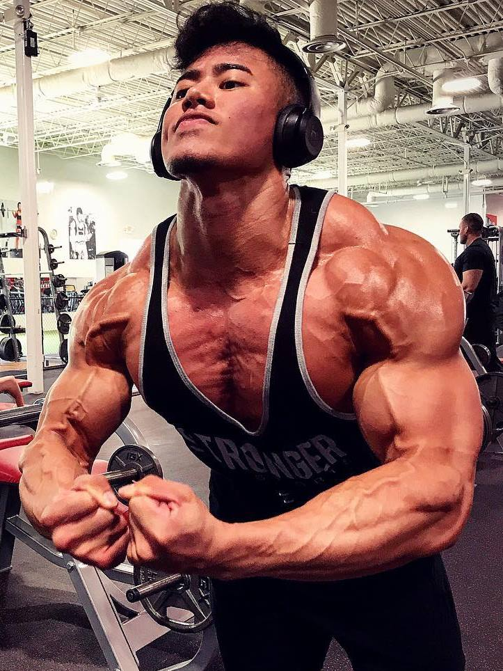 Steven Cao wearing black tank top, flexing in the gym