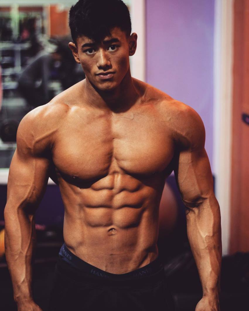 Steven Cao posing shirtless for the photo, looking lean and muscular