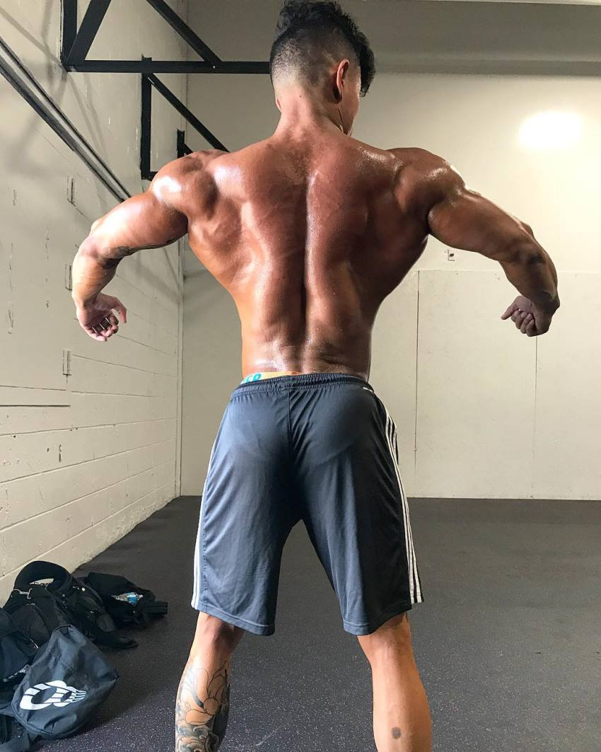 Steven Cao shirtless, spreading his lats wide