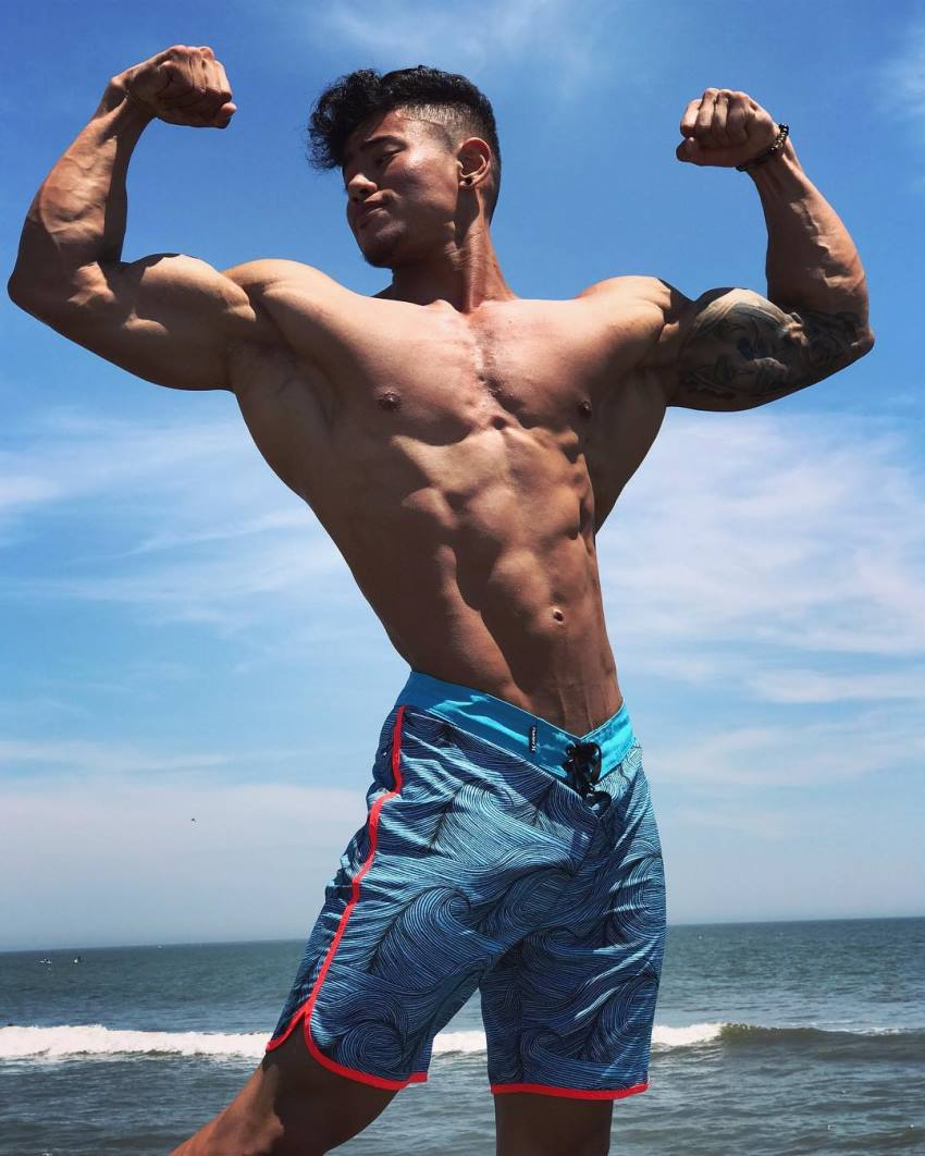 Steven Cao flexing his arms by the sea