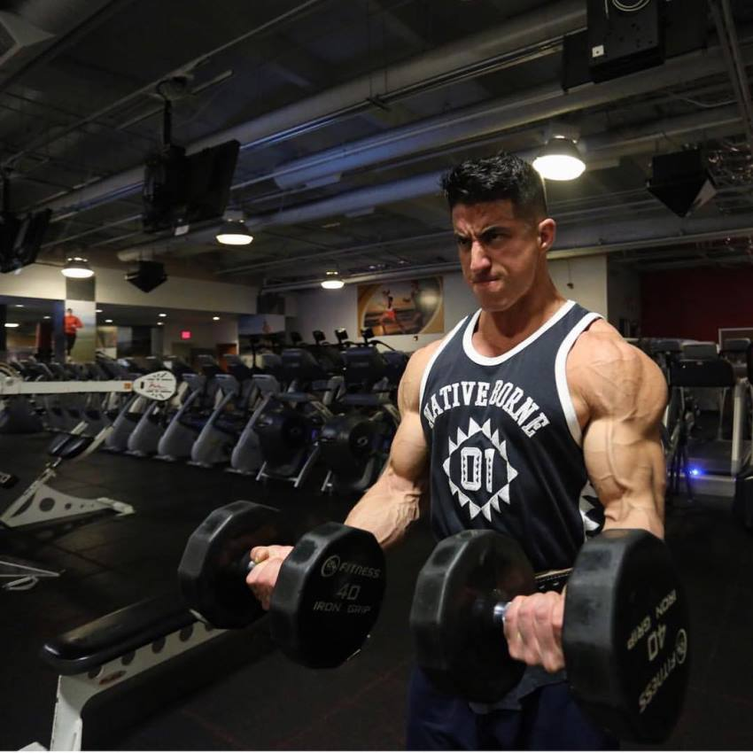 Tomas Echavarria doing dumbbell curls for his strong and ripped biceps