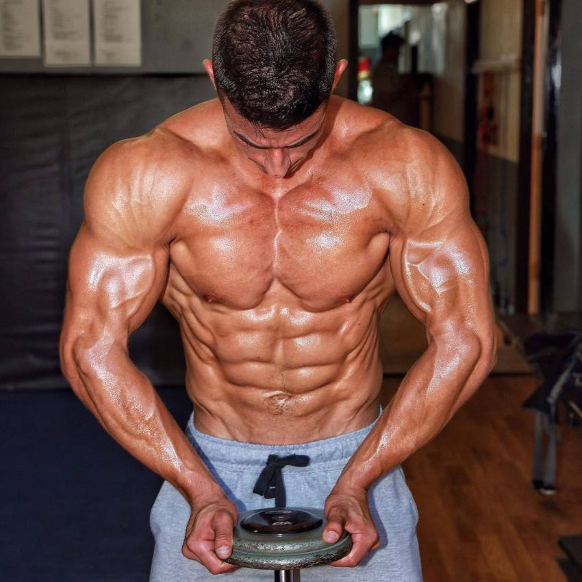 Tomas Echavarria holding a dumbbell and flexing his ripped muscles, showing hi shirtless upper body