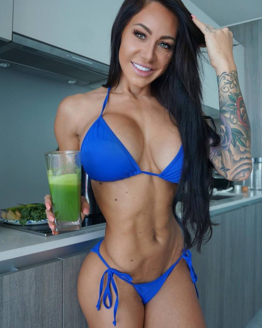 Venessa Nieto with a green smoothie in her hand, wearing a blue bikini, looking ripped and fit