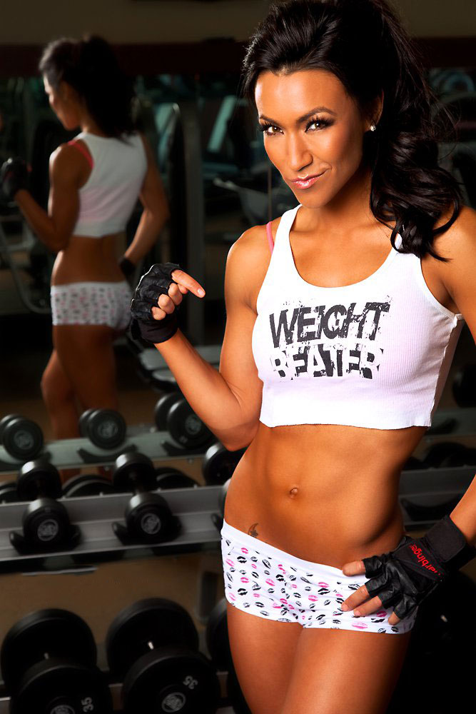Alex Zerega posing next to a dumbbell rack in a photo shoot.