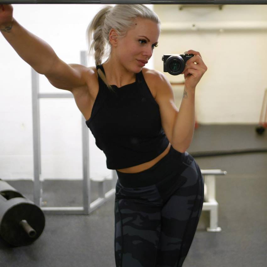 Anna Stålnacke taking a photo of herself by the weights, looking aesthetic and toned