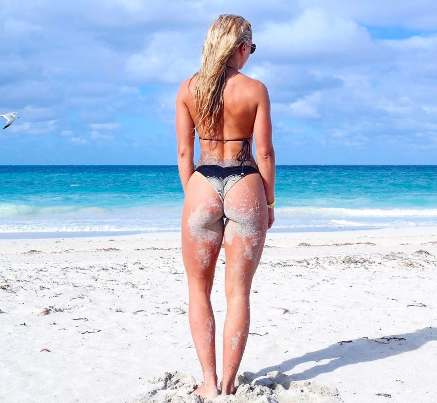 Anna Stålnacke standing in the sand by the sea, her glutes and legs looking curvy and toned