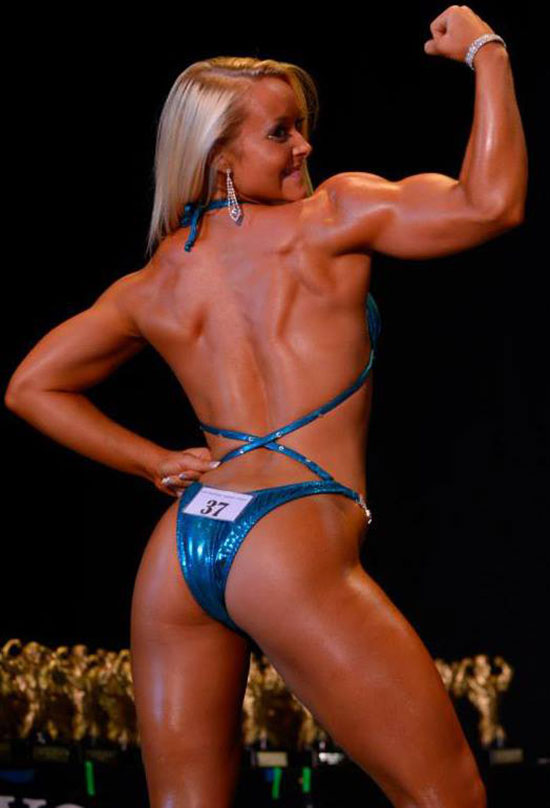 Ashley Lockaby flexing her bicep on the bodybuilding stage.