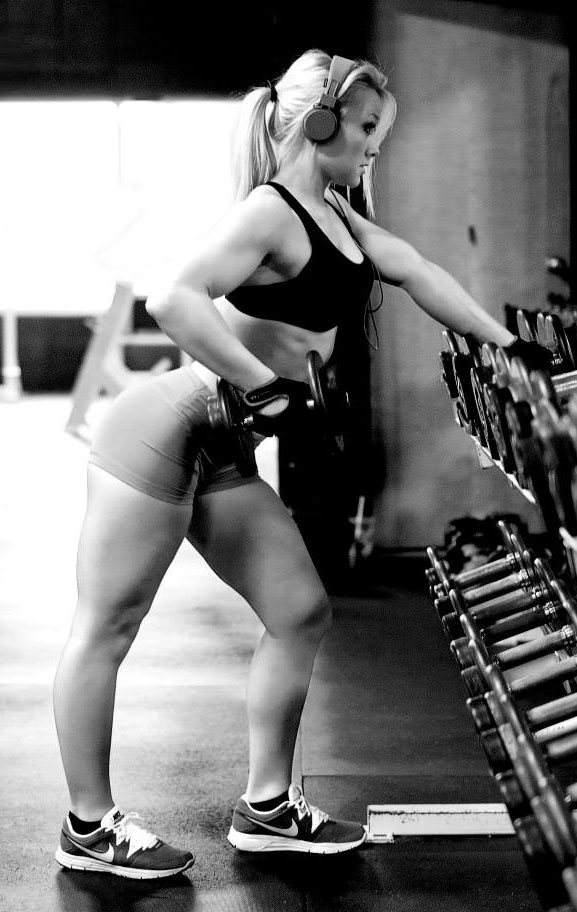 Ashley Lockaby exercising next to a dumbbell rack.