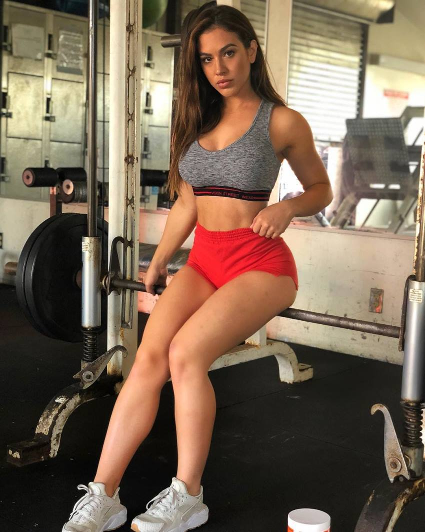 Chrysti Ane sitting in a gym posing for the camera