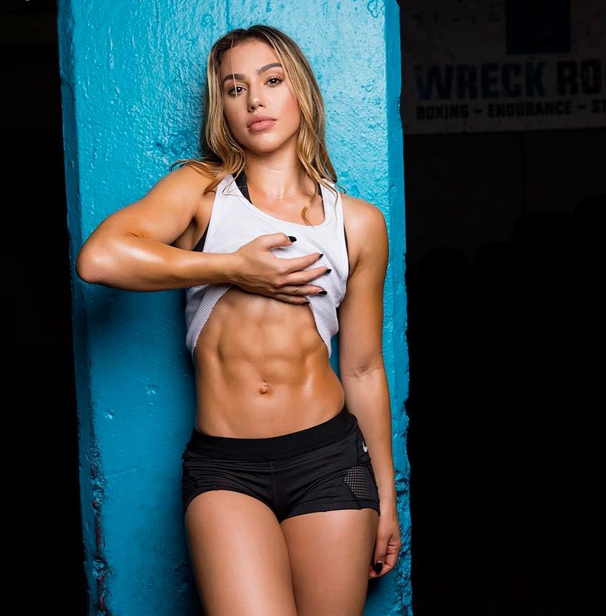 Chrysti Ane flexing her abs in a photo shoot looking fit and lean