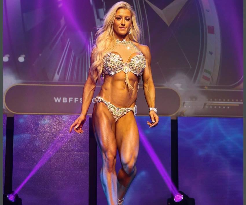 Clare Taubman stepping on the WBFF Pro Figure stage, looking conditioned and aesthetic