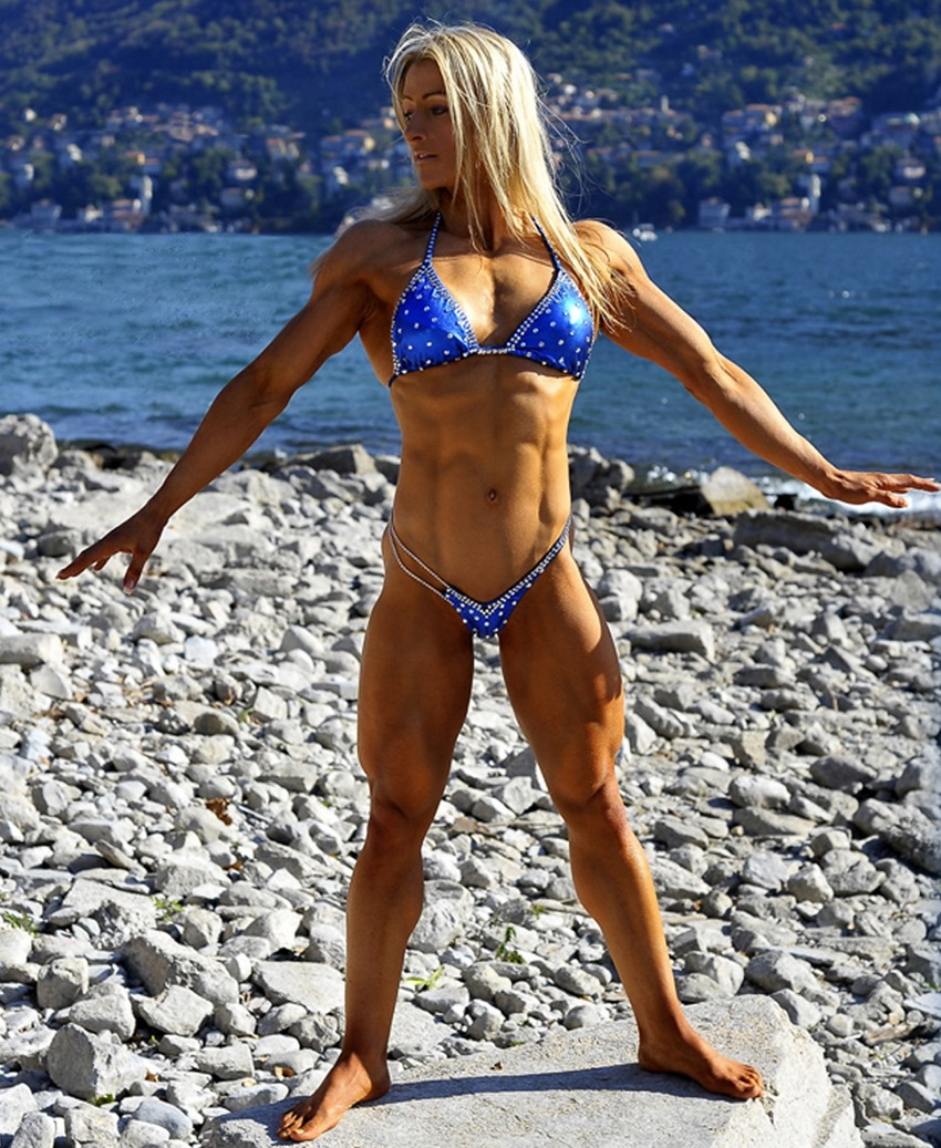 Clare Taubman posing in a blue bikini by the shore, looking ripped and muscular