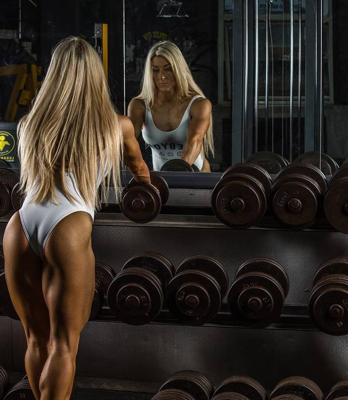Clare Taubman posing in a photo shoot, standing by a weight rack in a gym, holding onto dumbbells and looking at the mirror