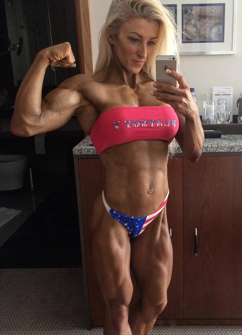 Clare Taubman flexing her biceps for a selfie, looking ripped and muscular