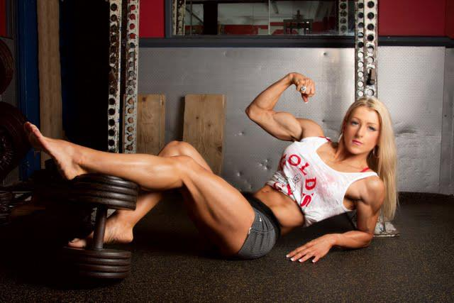 Clare Taubman lying down on the floor with her legs lying on a dumbbell, flexing her biceps for a photo