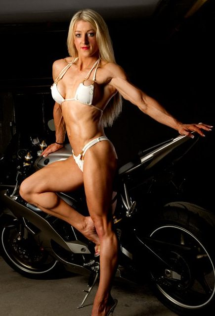 Clare Taubman wearing a white bikini, leaning on a motor bike, looking ripped and fit